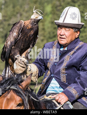 Issyk Kul, Kyrgyzstan - May 28, 2017 - Eagle hunter holds his eagle on his arm prior to the hunt - Stock Photo