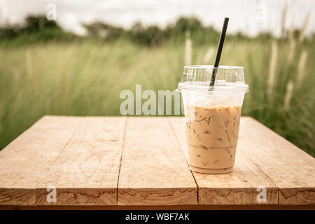Iced blended frappucino in plastic cup on wood table. Iced coffee. Vintage color tone - Stock Photo