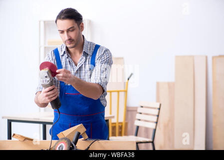 The young male carpenter working indoors - Stock Photo