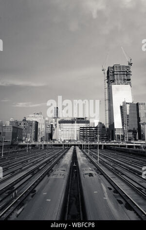Trains On Railroad Tracks In City Against Sky - Stock Photo