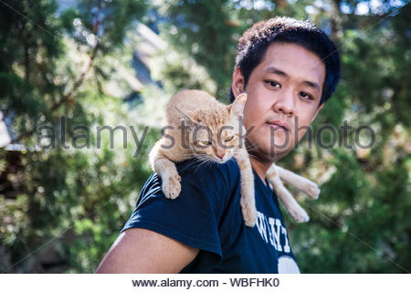 Portrait Of Asian Man With Cat On Shoulder - Stock Photo