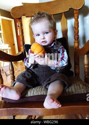 Full Length Portrait Of Boy Holding Pumpkin While Sitting On Chair In Living Room At Home - Stock Photo