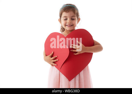 Happy little girl holds heart shaped cards in her hands. Feeling love concept - Stock Photo
