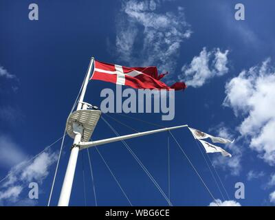 Low Angle View Of Danish Flag Waving On Sailboat Against Sea - Stock Photo