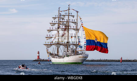 PORT WARNEMÜNDE, GERMANY - 11.08.2019: Sail training vessel 'Gloria' of the Colombian Navy is passing the light beacon - Stock Photo