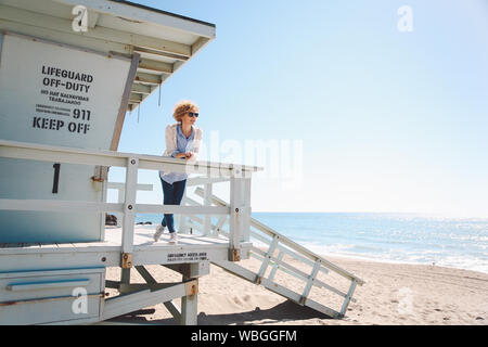 Woman Leaning On Railing Of Lifeguard Hut At Beach Against Clear Sky - Stock Photo
