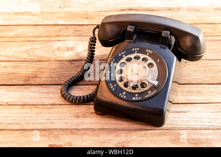 Retro rotary black telephone on wood table background. Old telephone with rotary dial. - Stock Photo