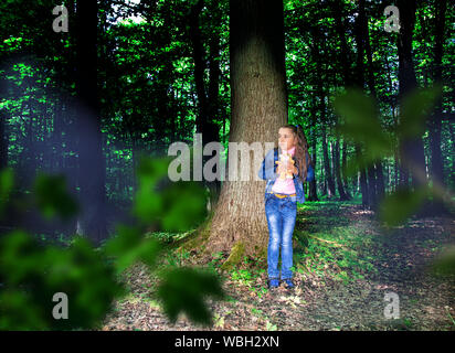little scared girl in denim costume standing near the tree in the dark woods - Stock Photo