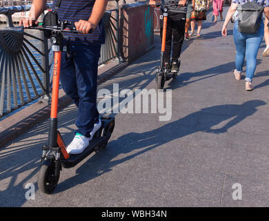 E-scooters between pedestrians in Berlin - Stock Photo