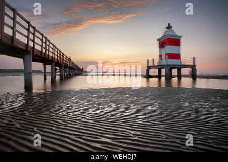 Wooden pier leading to a red lighthouse at sunrise in Lignano Sabbiadoro, Friuli, Italy - beach Stock Photo