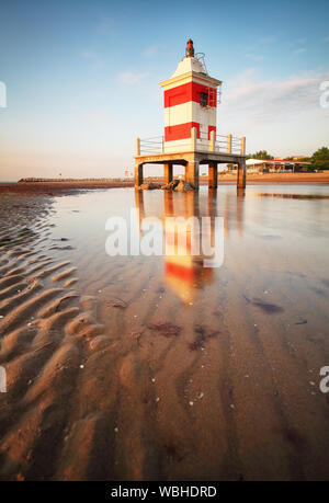 Red lighthouse at sunrise in Lignano Sabbiadoro on beach, Friuli, Italy Stock Photo