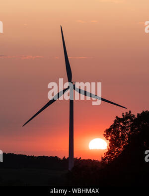 Crick, Northamptonshire, August 2019: The sun, partially obscured by clouds, sets in an orange sky behind a silhouetted wind turbine and tree. - Stock Photo