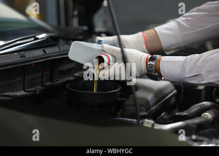 Male hand in white protective gloves with funnel - Stock Photo
