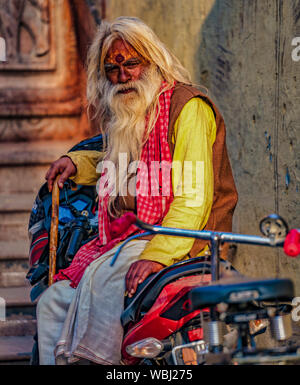 Vrindavan, India - February 22, 2018 - Old man sits on a motorcycle while holding a wooden cane - Stock Photo