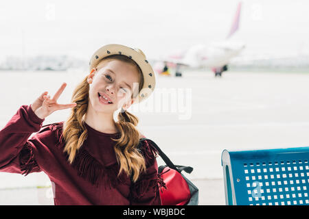 cute preteen kid sticking out tongue and showing Peace Sign in airport - Stock Photo