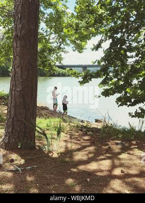 High Angle View Of Friends Standing On Field While Fishing In Lake - Stock Photo