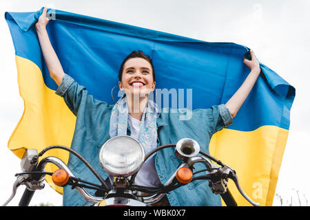 low angle view of beautiful girl sitting on scooter, smiling and holding Ukrainian flag - Stock Photo
