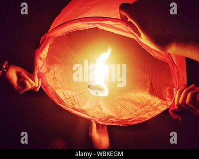 Low Angle View Of Friends Releasing Lit Paper Lantern At Night - Stock Photo