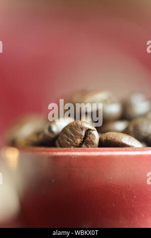 Close-up Of Roasted Coffee Beans In Red Cup - Stock Photo