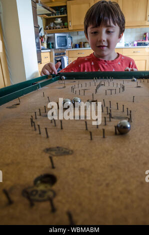 Cute Boy Playing Bagatelle At Home - Stock Photo