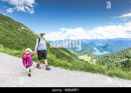 Mother With Daughter On Mountain Against Sky - Stock Photo