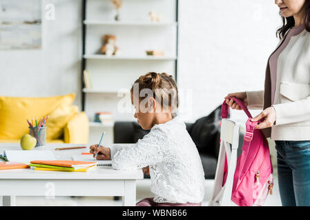 cropped view of mother holding pink backpack near daughter drawing at home - Stock Photo