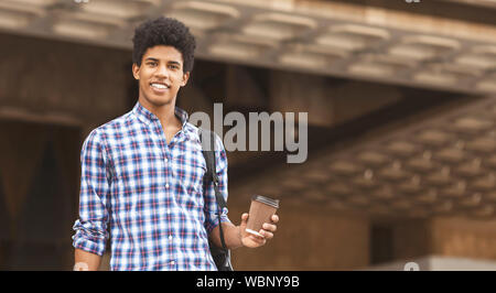 African american student smiling to camera holding cup with coffee - Stock Photo