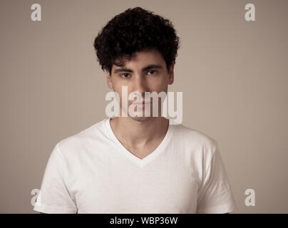 Close up portrait of attractive, confident young man looking neutral, relaxed and serious in People facial expressions, human emotions, Success and ed - Stock Photo