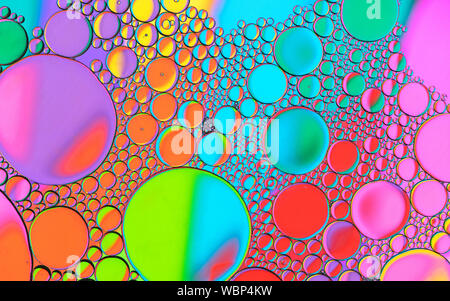 Multicoloured coloured bubble patterns formed by oil floating on water - Stock Photo