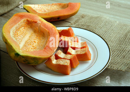 Ripe Seedless Papaya fruit pieces in a white plate on wooden background - Stock Photo