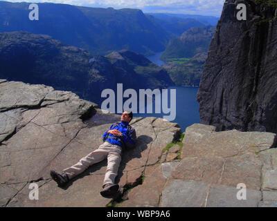 Full Length Of Hiker Lying On Preikestolen - Stock Photo