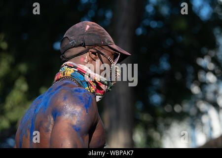 A black man at Notting Hill carnival covered in blue paint. - Stock Photo