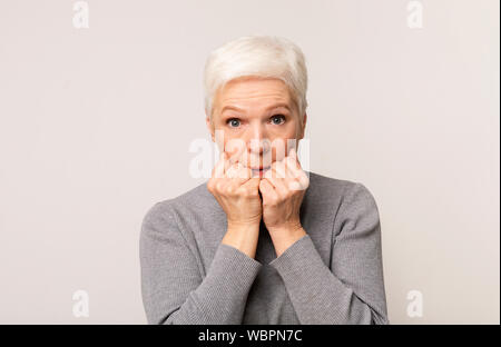 Scared elderly woman looking at camera, covering mouth with fists - Stock Photo