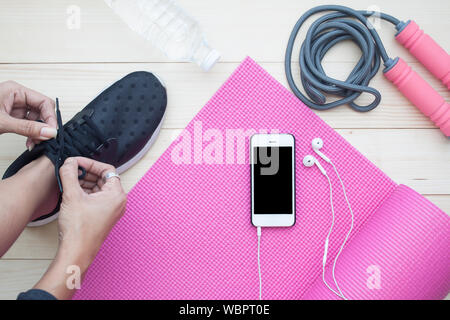 Low Section Of Woman Wearing Shoe By Smart Phone On Hardwood Floor - Stock Photo