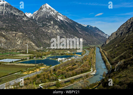 In the Rhone valley near Martigny with Lake Lac du Rosel, motorway service station Relais du St-Bernard, motorway A9 and the canalized Rhone river - Stock Photo