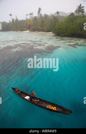 Melanesian children paddle their dugout canoe in the rain amid the beautiful Solomon Islands. This Melanesian region is part of the Coral Triangle.
