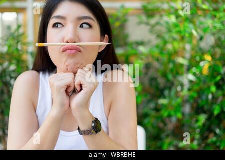Close-up Of Playful Young Woman Balancing Pencil On Lips - Stock Photo