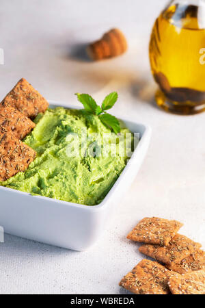 Hummus pasta from peas and mint in a bowl with crackers and olive oil. Green hummus sauce. Healthy snack. Vegan meal. Vegetarian food. - Stock Photo