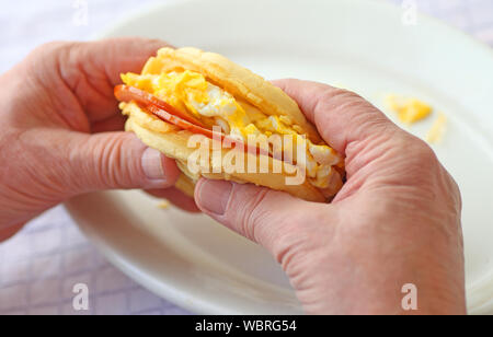 Waffle sandwich of Canadian bacon and scrambled eggs in a man's hands - Stock Photo