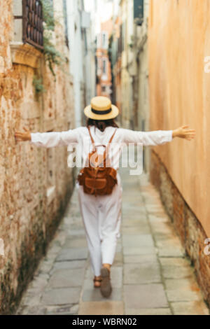 woman in white clothes in straw hat and brown leather backpack walking by city street