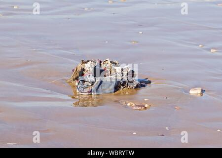 Clothes and rubbish washed up onto sand beach by the Atlantic Ocean, Agadir, Morocco - Stock Photo