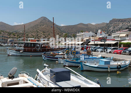 Crete, Greece.  Elounda on the Gulf of Mirabello one of Crete's expensive holiday regions. Fishing boats on the harbour. - Stock Photo