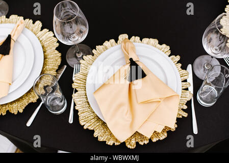 A dining white plate and a plate-decoration of golden metal on the table at the restaurant. A fabric napkin made of golden atlas and black brush. - Stock Photo
