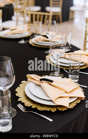 Modern design of a festive banquet in the restaurant with golden details and luxury dishes. Serving a table for guests at a wedding - Stock Photo