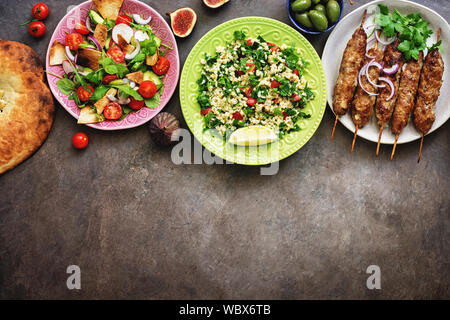 Traditional Middle Eastern and Arabian cuisine on a dark rustic background, border. Meze party food. Top view, flat lay, overhead,copy space.
