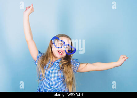 Fashion eyewear. Power of love. Kid girl heart shaped eyeglasses. Girl adorable smiling face fall in love. Child charming smile blue background. Kid happy lovely enjoy childhood. Heart symbol of love. - Stock Photo