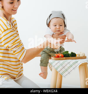 Active restless infant child is presented food - Stock Photo