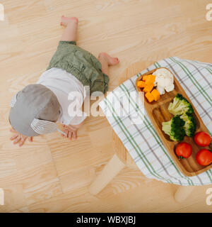 Active restless infant child is presented food. Crawls near his dinner setting. - Stock Photo
