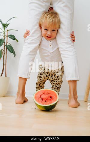 Little toddler boy, mother's legs arch and watermelon half slice - Stock Photo
