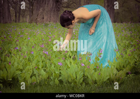 Young Woman Touching Plants Growing On Field In Forest - Stock Photo